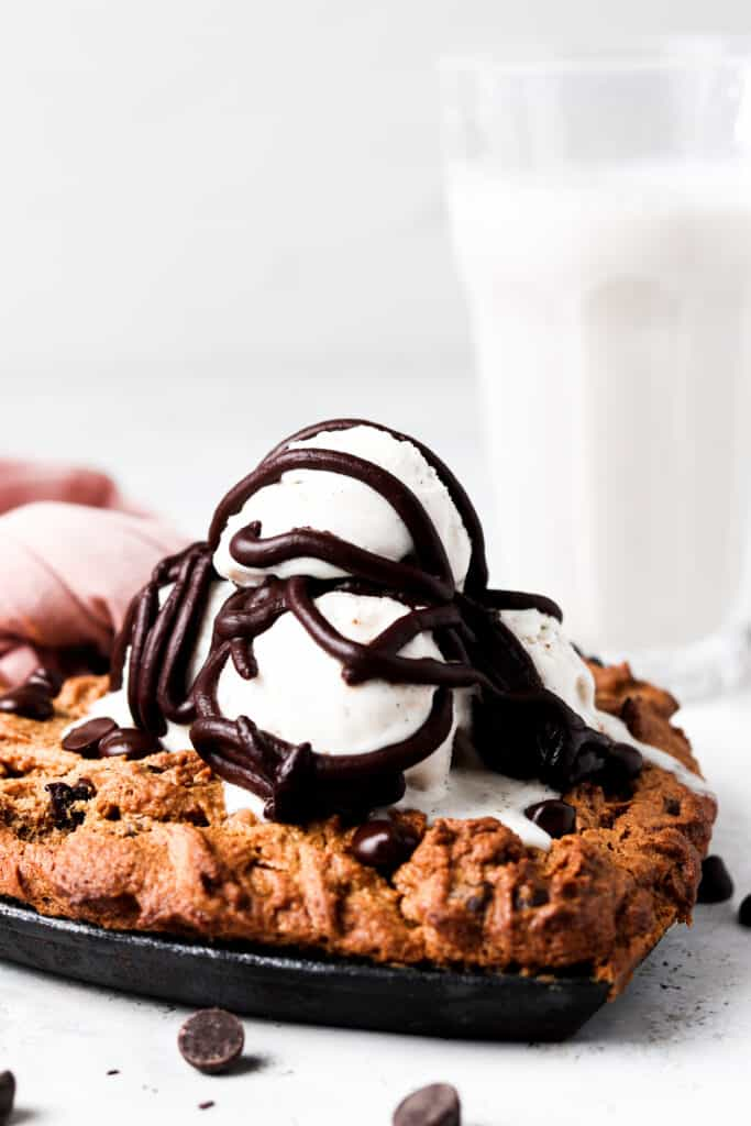 vegan skillet cookie with ice cream and chocolate ganache on top with a glass of milk