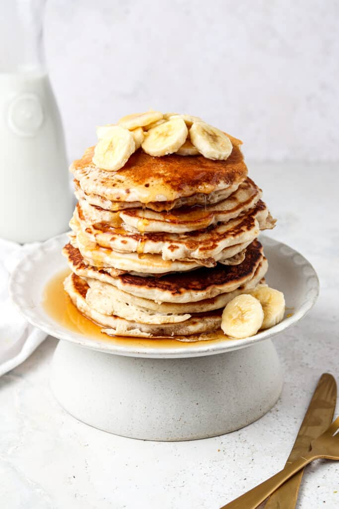 3 ingredient protein pancakes stacked on a plate with bananas and maple syrup