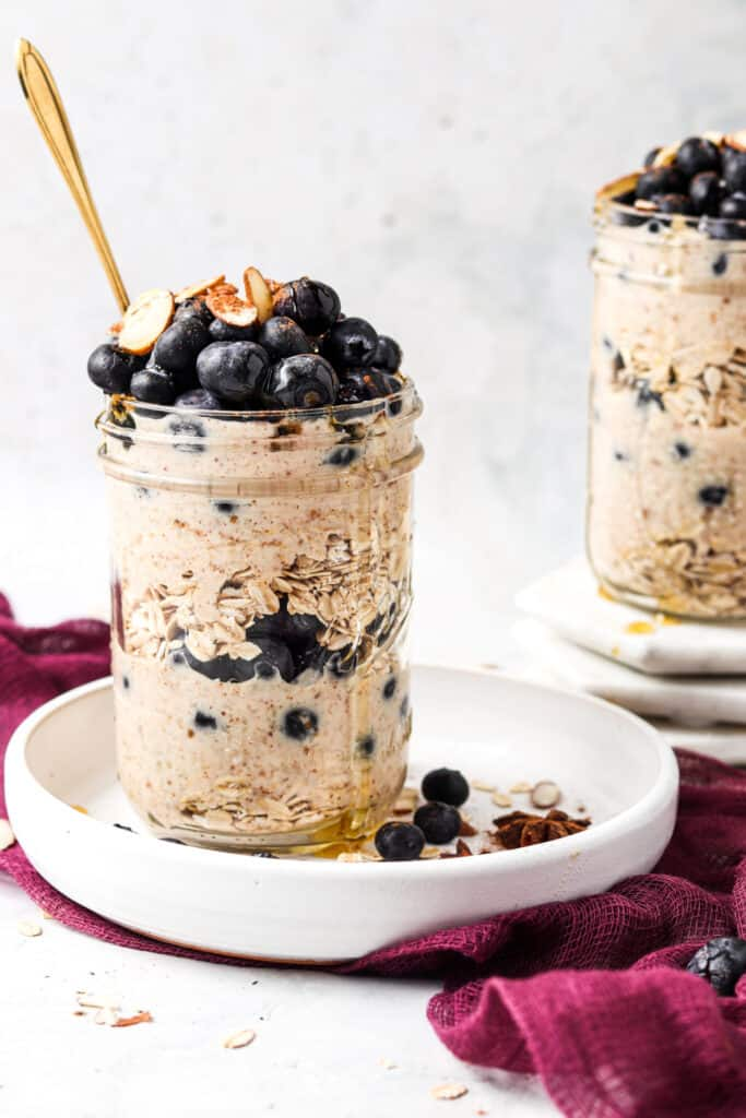 blueberry banana overnight oats in a mason jar on a white plate with a gold spoon