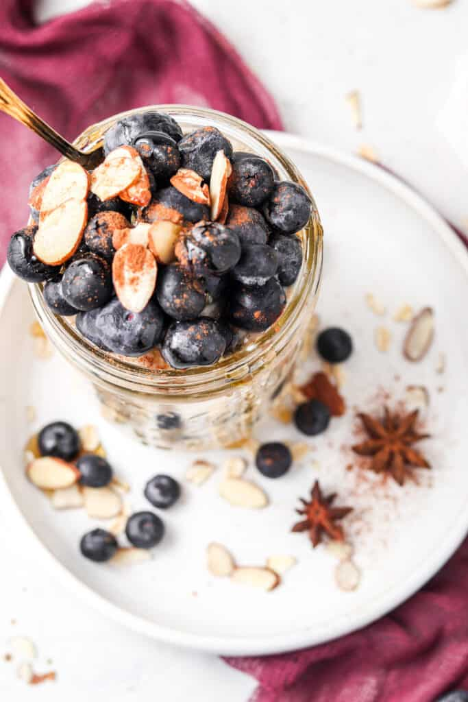 blueberry banana overnight oats overhead shot with white plate and purple cloth