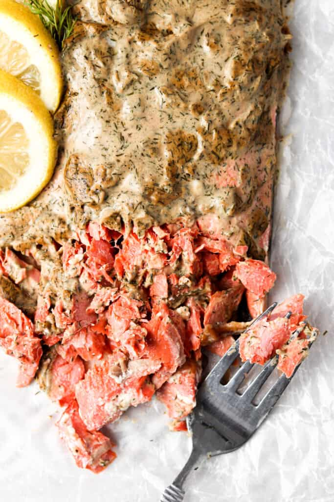 whole30 salmon with dijon mustard and ghee on top with lemons and a fork
