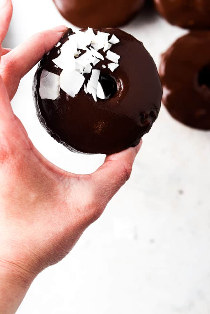 person holding a gluten free donut with chocolate ganache and coconut