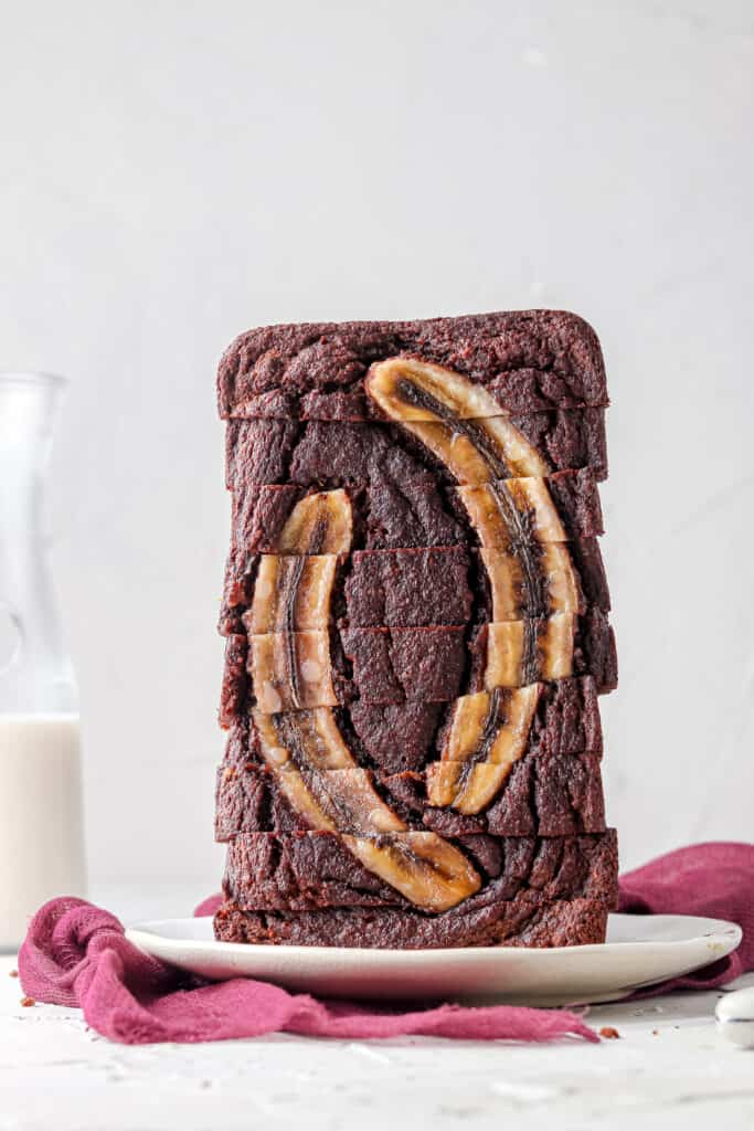 whole chocolate banana bread stacked on a white plate
