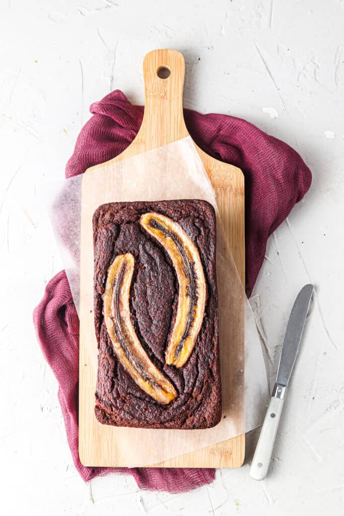 whole chocolate banana bread on a wooden tray with a knife