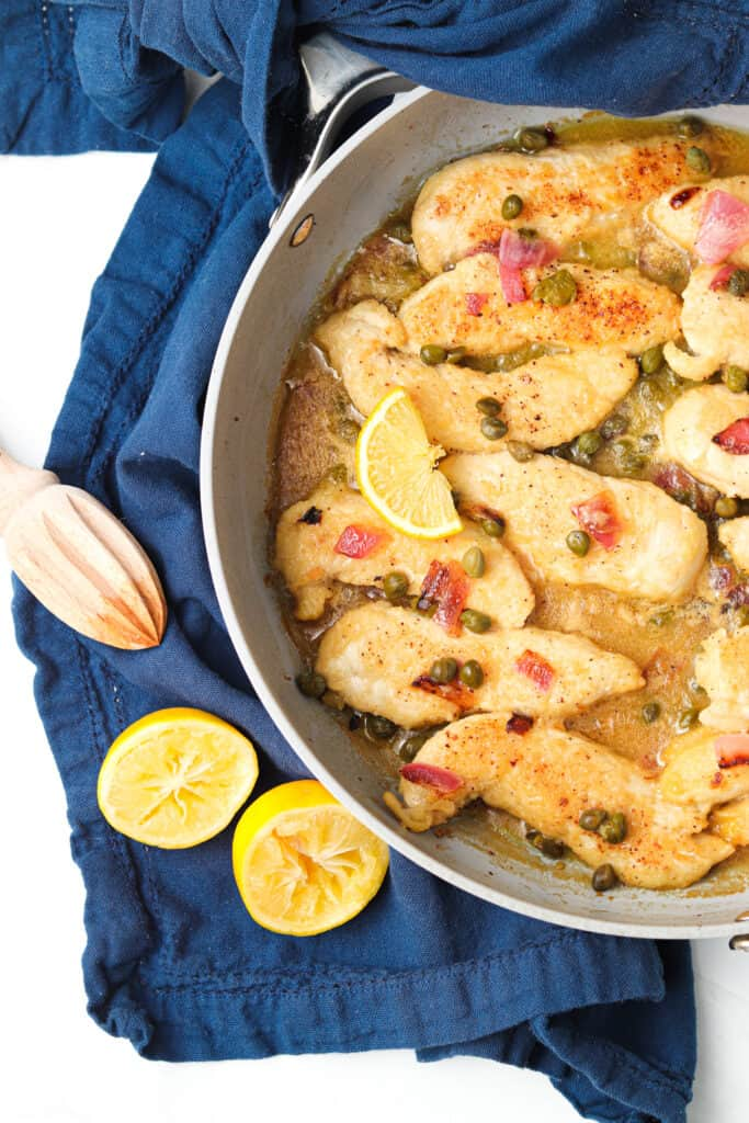 chicken piccata in a pan with lemon wedges