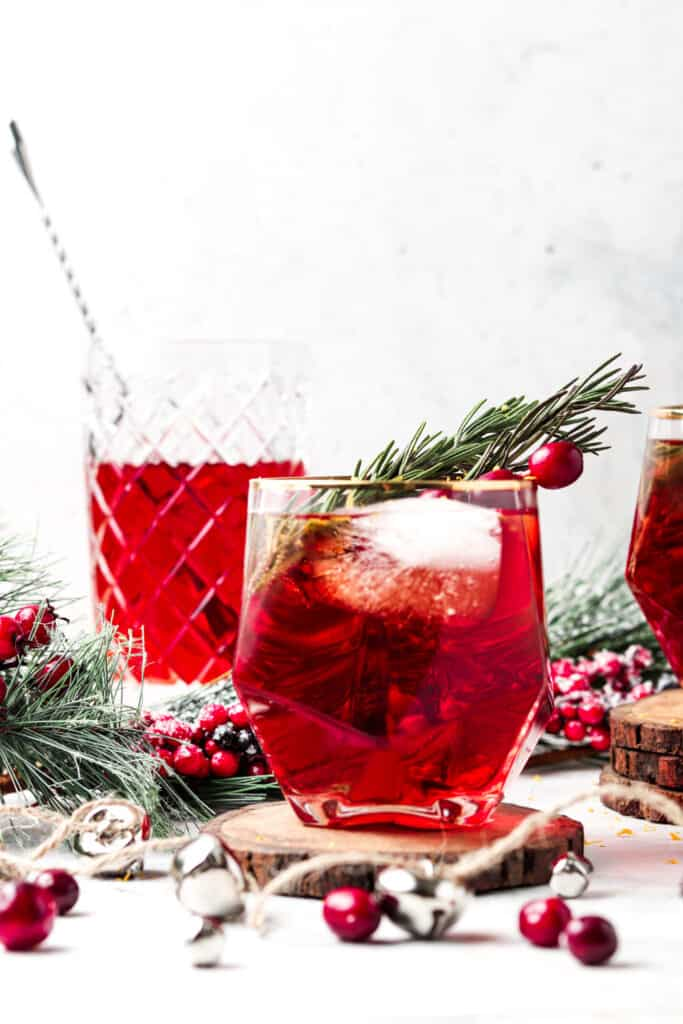 cranberry mocktail with fresh rosemary in a cocktail glass with Christmas decorations
