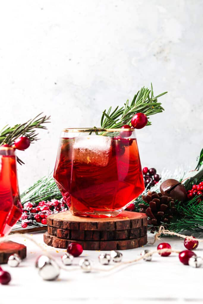 cranberry mocktail on 3 wooden coasters in a christmas setting
