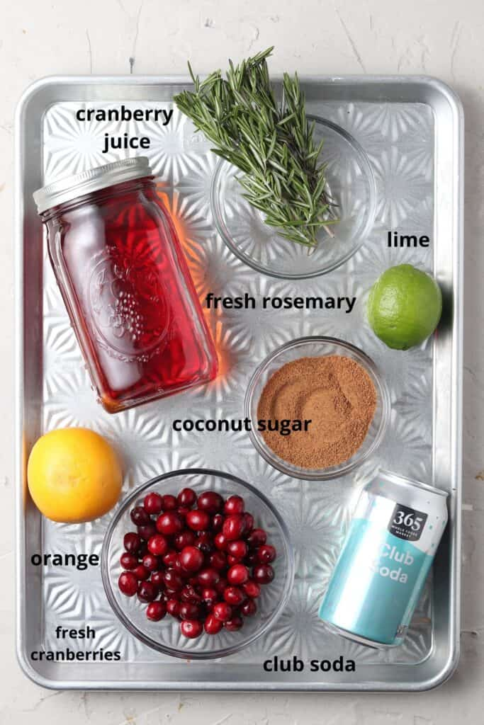 cranberry mocktail ingredients on a silver tray