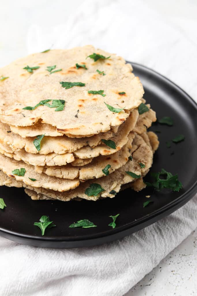 aip tortillas on a black plate with fresh herbs