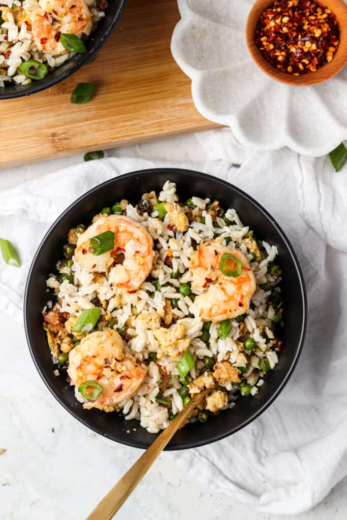 shrimp fried cauliflower rice in a black bowl with a spoon and red pepper flakes