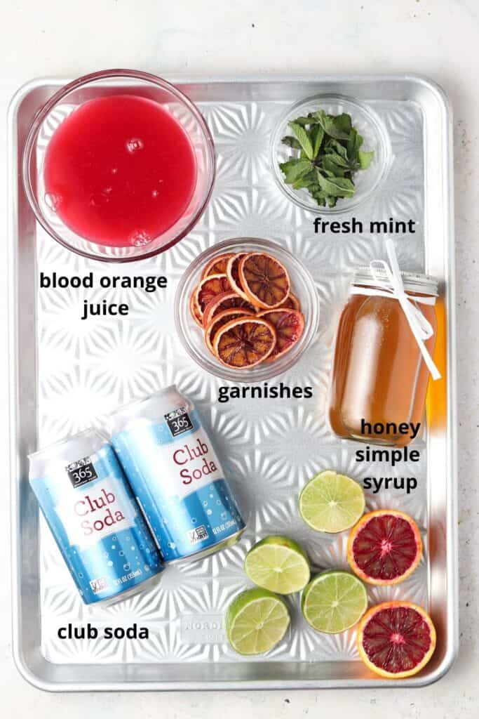 blood orange mojito mocktail ingredients on a metal tray
