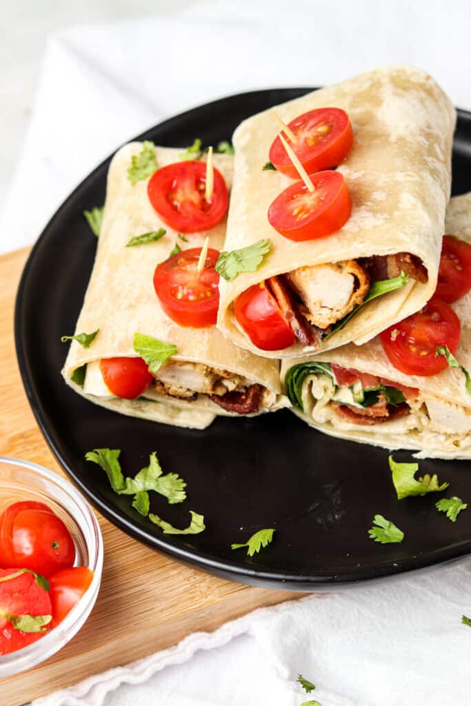 crispy ranch wraps on a black black with tomatoes