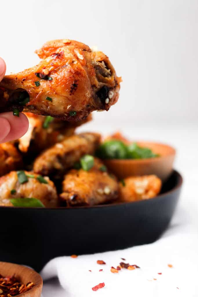 holding garlic butter wings over blue bowl