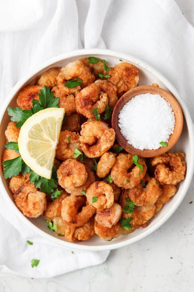 crispy shrimp on a white plate with a lemon and sea salt