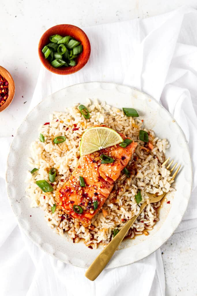 far away shot of honey sriracha salmon on a plate with rice