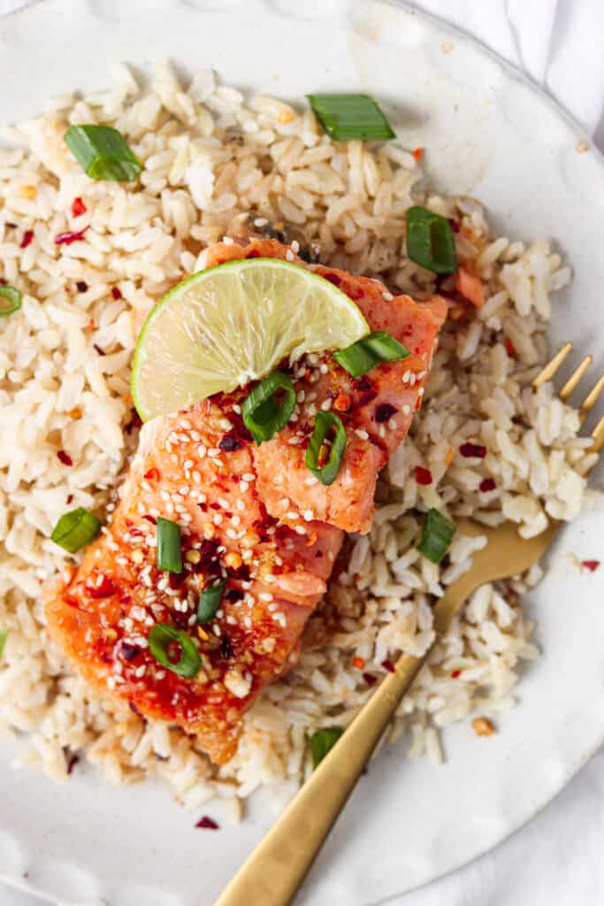 honey sriracha salmon on a plate with rice and a fork