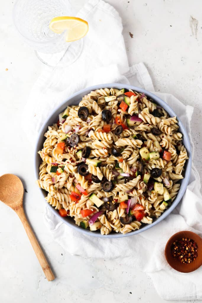paleo pasta salad in a blue bowl with a glass and red pepper flakes