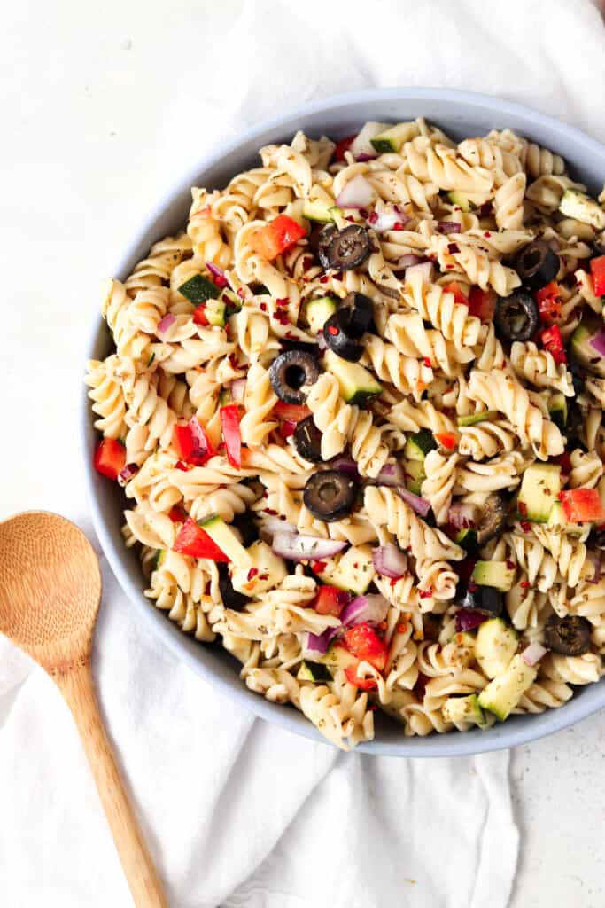paleo pasta salad in a blue bowl with a wooden spoon