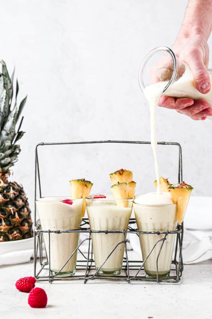 man pouring paleo pina colada into a glass with 6 other glasses