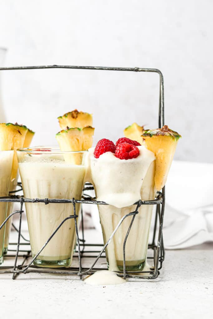 paleo pina coladas in 6 glasses with pineapple on top