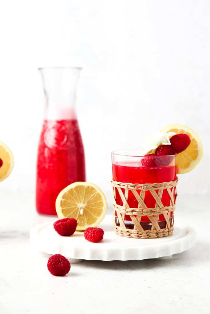 paleo raspberry lemonade in a clear glass with lemon garnishes