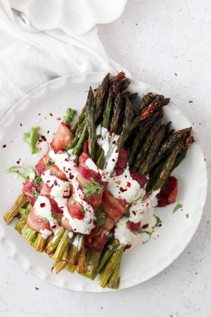 bacon wrapped asparagus with garlic aioli on a plate with fresh herbs