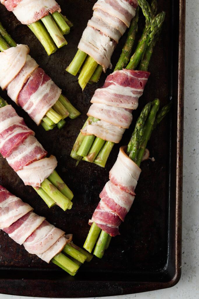 raw bacon on a tray with asparagus