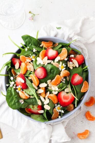strawberry poppyseed salad with oranges in a blue bowl