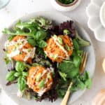 salmon cakes on a bed of greens with aioli sauce on top
