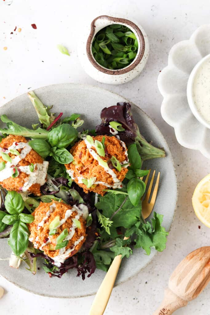 whole30 salmon cakes on a bed of greens