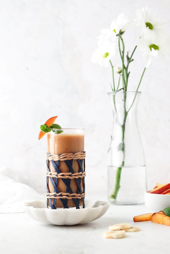 peach smoothie with flowers in the background