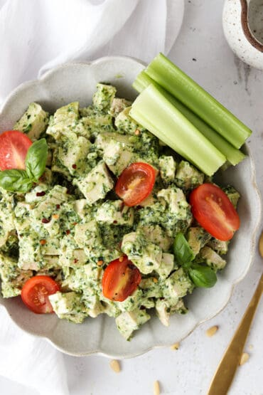 pesto chicken salad in a bowl with tomatoes and celery