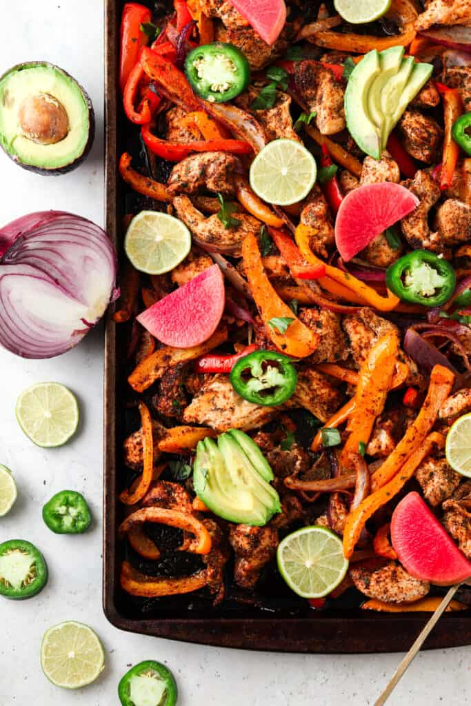 chicken fajitas on a sheet pan with peppers