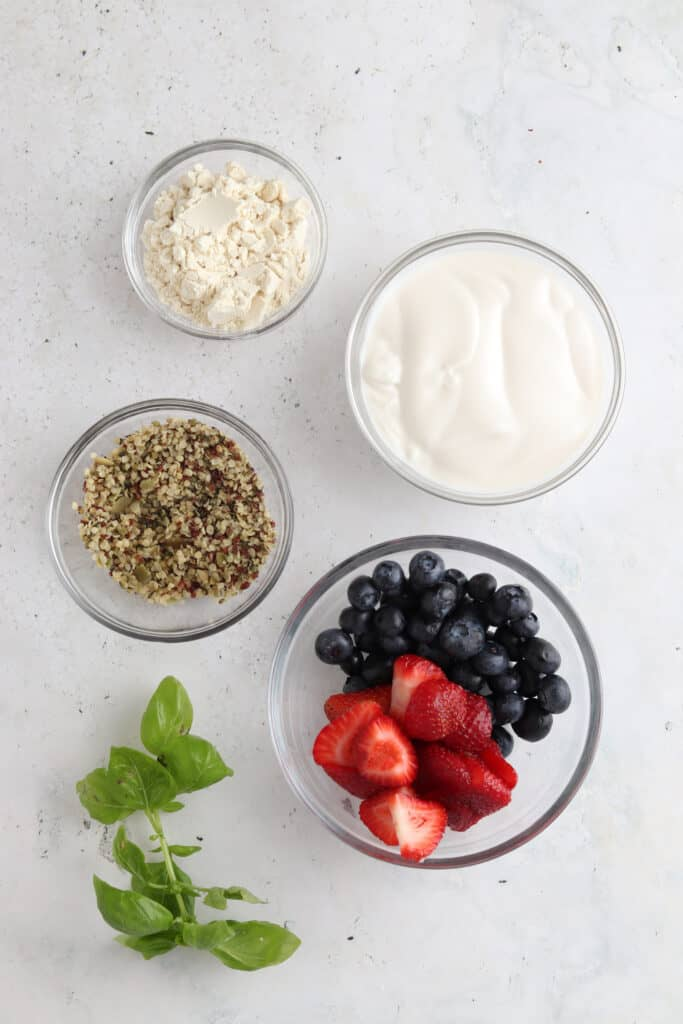blueberry and strawberry smoothie ingredients laid out in bowls