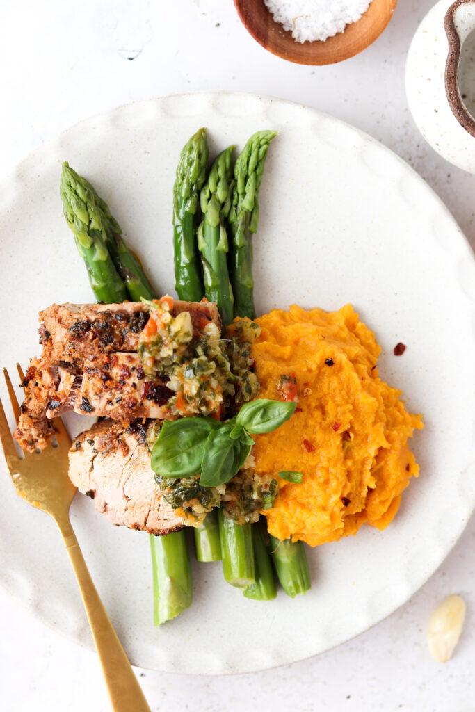 overhead shot of whole30 pork tenderloin with sweet potato mash and asparagus