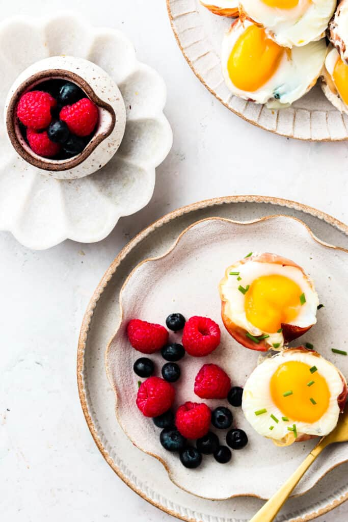 Prosciutto Egg Cups on a plate with fruit