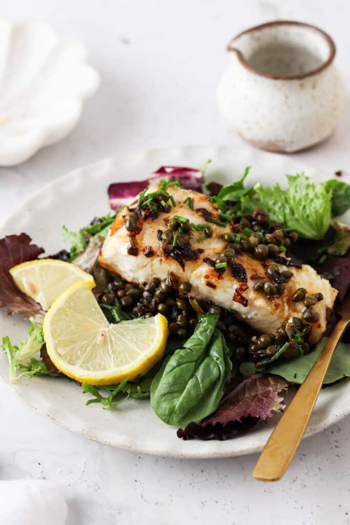 pan seared sea bass on a plate with greens and lemon