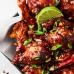 peanut butter and jelly chicken wings on a plate with limes