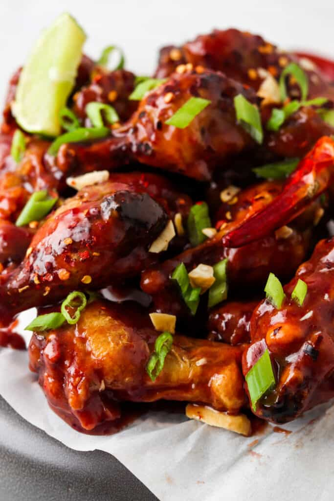 close up shot of chicken wings with green onions and peanuts on top