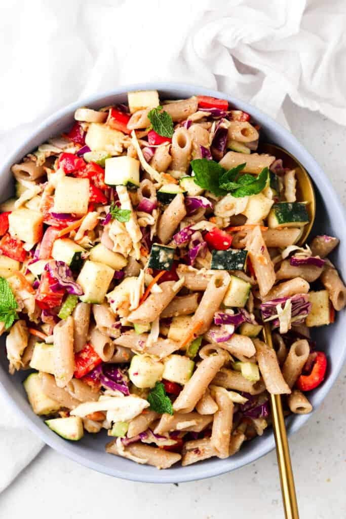 thai pasta salad in a blue bowl with a gold spoon