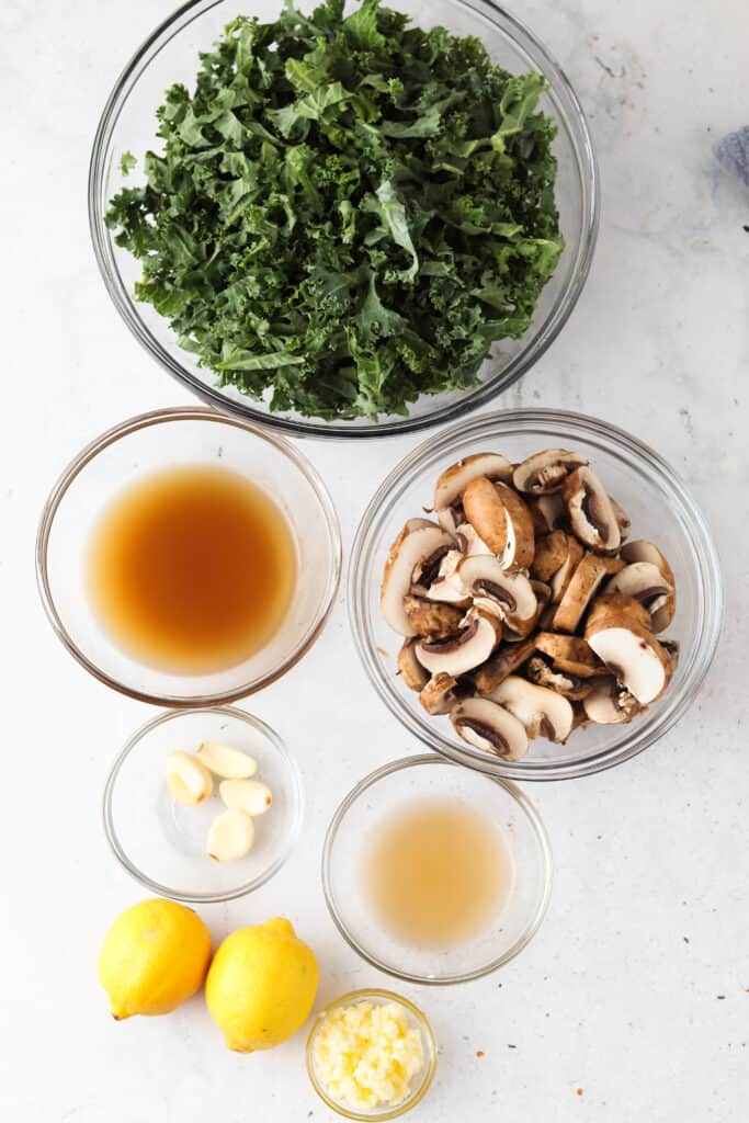 sauteed kale and mushroom ingredients laid out in bowls