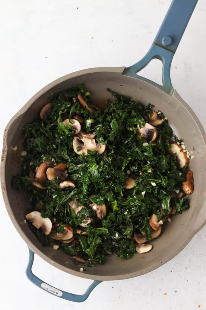 kale and mushrooms in a pan