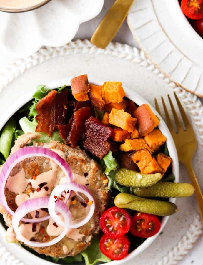deconstructed burger bowls with sweet potatoes, pickles, tomatoes, and bacon